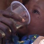 Een kind krijgt de oplossing met MMS te drinken tijdens een van de veldproeven van Sam LIttle (bron: Facebook)